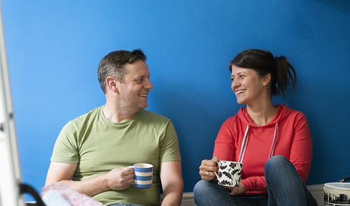 Couple drinking tea after painting a room