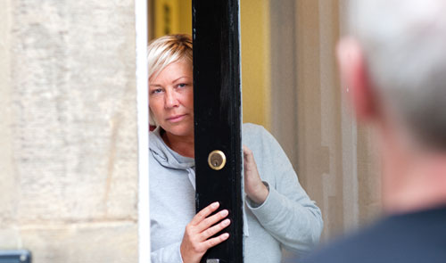 woman opening door to bailiff