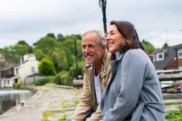 Older couple sat on a bench along a canal