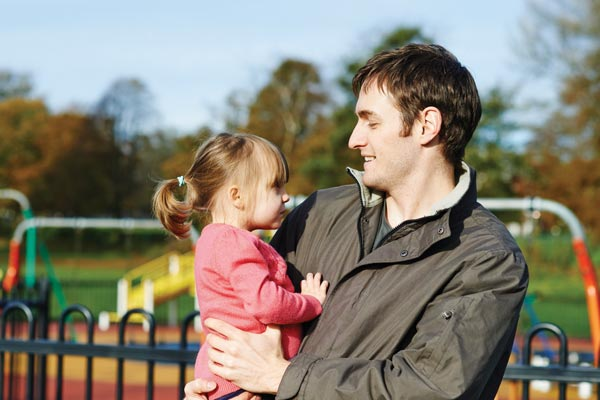 man with daughter in park