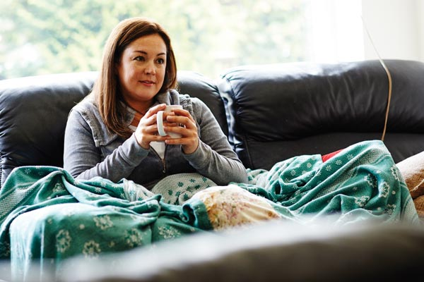woman on couch with cup of tea