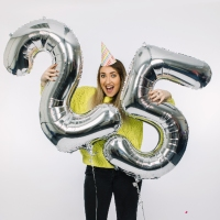 woman holding number 25 as a silver balloon