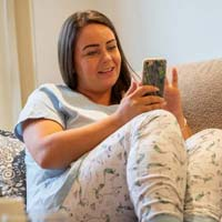Younger woman on sofa looking at her phone
