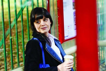 Woman at bus stop with coffee