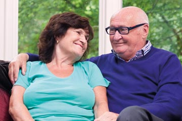 An elderly couple at home on a sofa smiling at each other