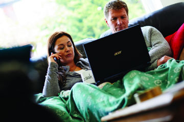 Couple sat on their sofa with laptop and phones