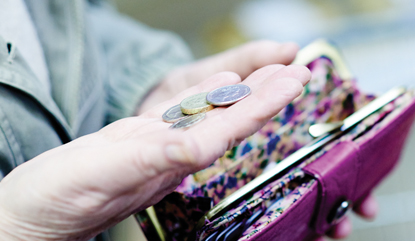 woman holding coins from her purse
