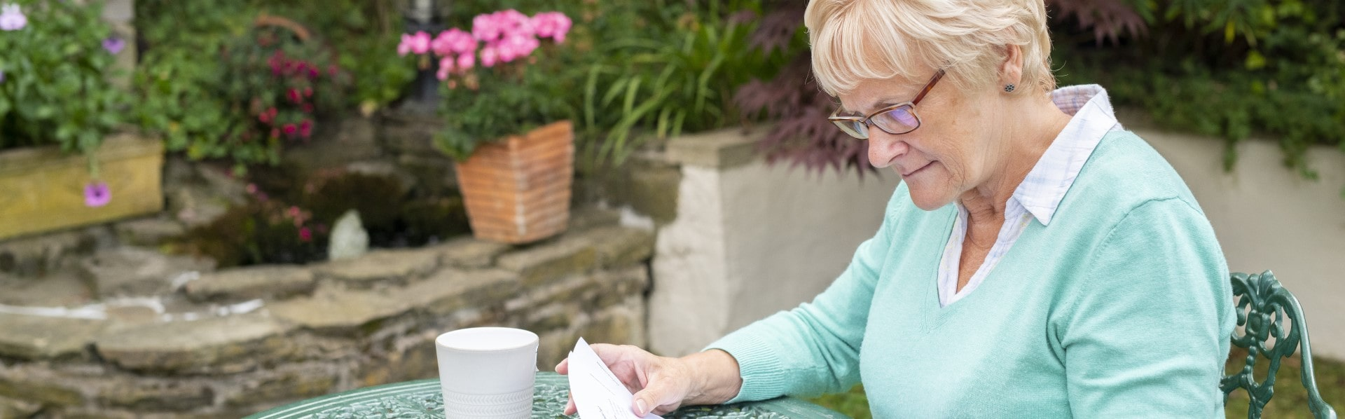 Woman looking at bills in her garden