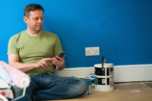 man sat on the floor next to paint tin