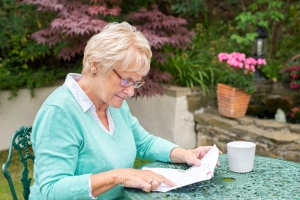 woman reading bills in garden