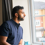 man looking outside window at home