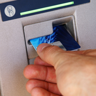 putting a bank card into a cash machine